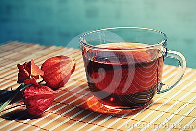 Cup of tea and physalis on a bamboo table cloth