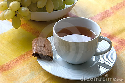 Cup of tea with a piece of biscuit and grapes.