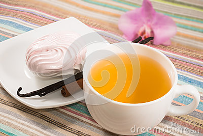Cup of tea and pink marshmallow on a saucer with a vanilla