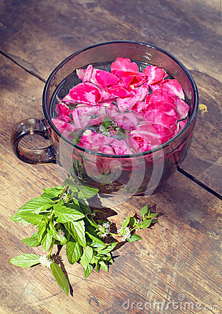 The cup of tea with rose petals and mint