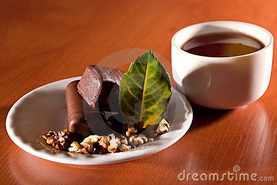 Cup of tea and saucer with sweet dessert