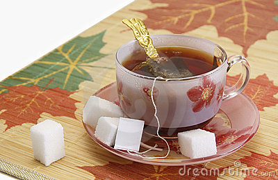 Cup of tea and sugar pieces