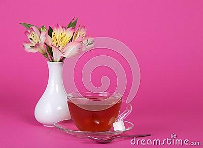 Cup of tea and sugar on saucer, teaspoon, vase