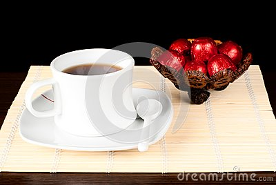 A cup of tea with sweets.