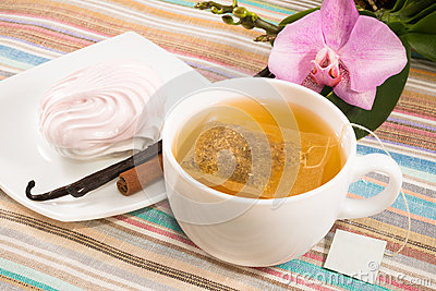 Cup of tea with tea bag and pink marshmallow on a saucer with a vanilla, cinnamon