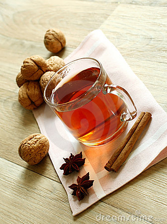 Cup of tea and walnuts on wooden