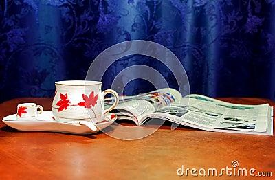Cup und geöffnete Zeitschrift