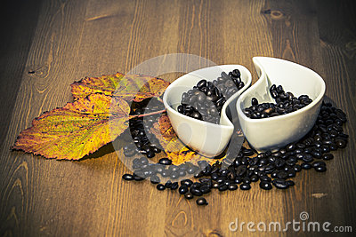 Cups with coffee beans on a wooden table