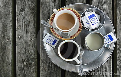 Cups of coffee, jug of milk, sugar on wooden table