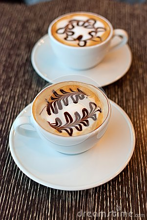 Cups of coffee with tree pattern in a white cup