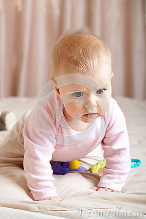 Curious baby girl crawling on bed, closeup shot