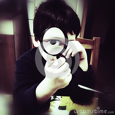 Curious boy with magnifier