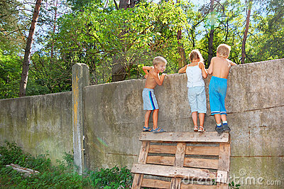 Curious children spying over the fence