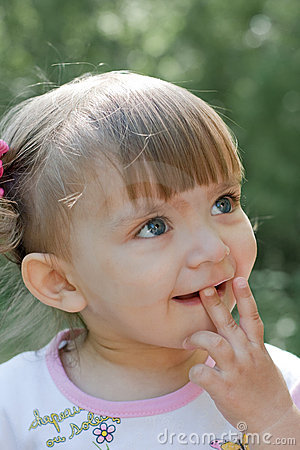 Curious little girl outdoor portrait in Summer