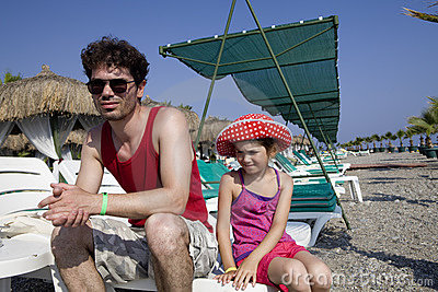 Curl father wearing sun glasses and his daughter
