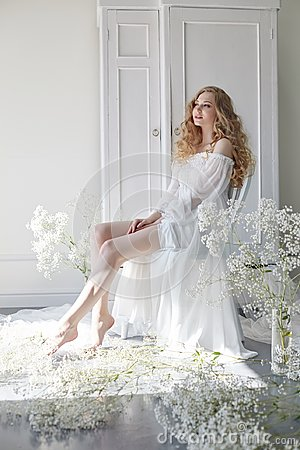 Free Curly Blonde Romantic Look, Beautiful Eyes. White Wildflowers In Hands. Girl White Light Dress And Curly Hair, Portrait Of Woman Stock Photo - 119476970