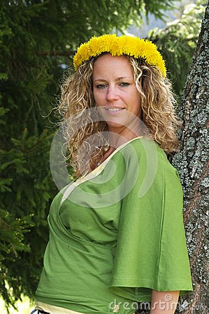 Curly girl with dandelion chain on head