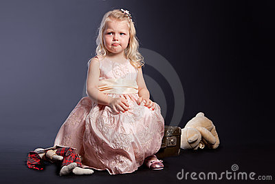 Curly girl in pink dress sitting on old suitcase