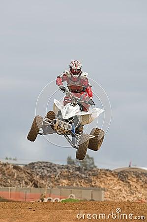 Curseur de motocross d ATV au-dessus d un saut Photographie éditorial