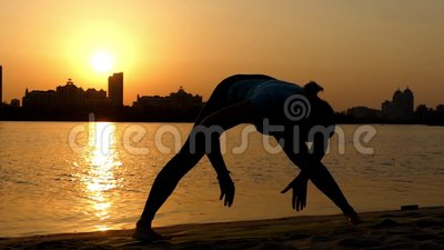 Curva delantera Ancho-Legged de la actitud de la yoga de la práctica de la muchacha la acción en la puesta del sol en almacen de video