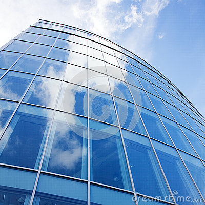 Curved facade of modern glass blue office and clouds