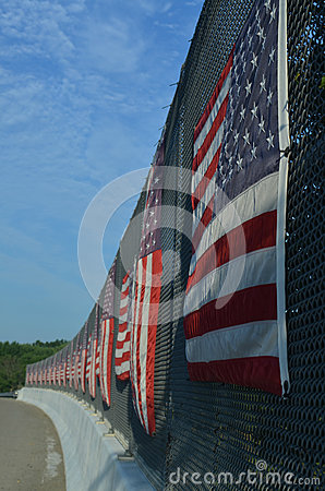 Free Curved Line Of American Flags On Sunny Side Of Highway Overpass Fence Stock Image - 74878491