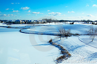 Curvy landscape on the snow covered golf course and pond.