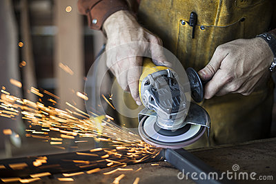 Custom furniture worker grinds weld seam on steel frame. Stock Photo