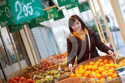 Customer buying tangerines at market