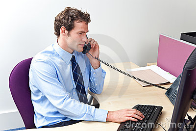 Customer care worker in an office on the telephone