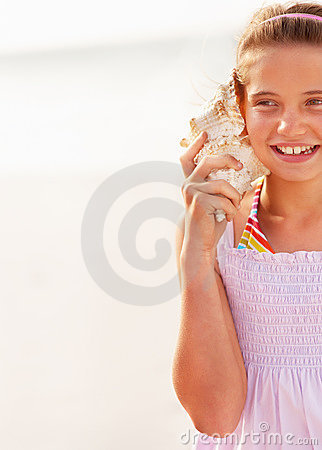 Cut image of a young girl hearing a conch shell