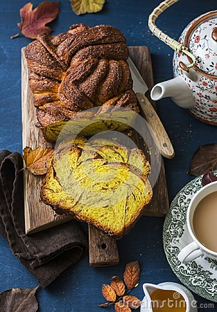Free Cut The Pumpkin Brioche Cinnamon On Rustic Wooden Chopping Board, Tea With Milk And A Teapot On A Blue Background, Top View. Royalty Free Stock Photos - 102565678