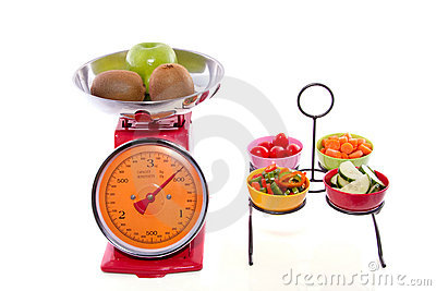 Cut vegetables in bowls fruit on kitchen scales