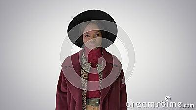 Cute afro model in jas die de hoed aanraakt op gradiëntachtergrond stock video