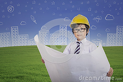 Cute architect boy holding plan outdoor