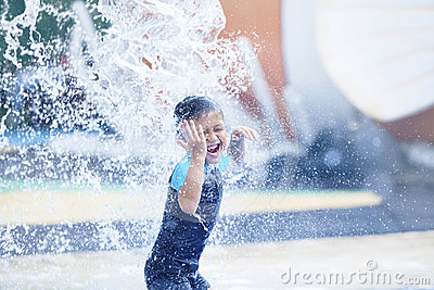 Cute asian boy playing at water park