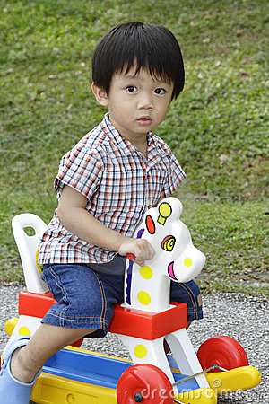 Cute Asian boy on a toy horse
