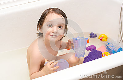 Cute baby bathes in a bathroom with toys