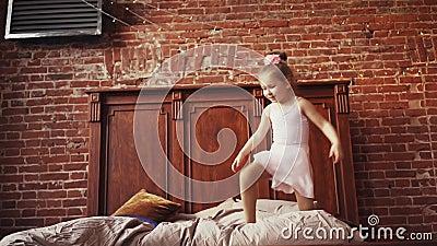 Cute baby girl blonde die op bed springt Kindertijd Geluk en vreugde Langzame beweging Afschieten op de Steadicam stock video
