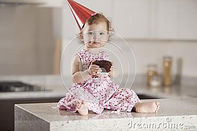 Cute baby girl eating cake