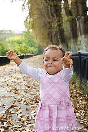 Cute baby girl excited among autumn leaves