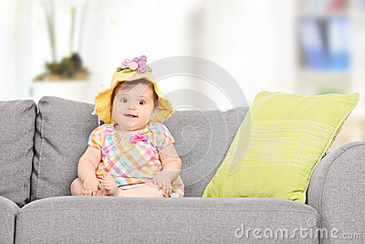 Cute baby girl with a knitted hat sitting on sofa