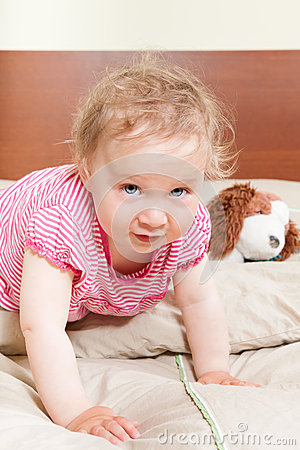 Cute baby girl looking into camera on bed.