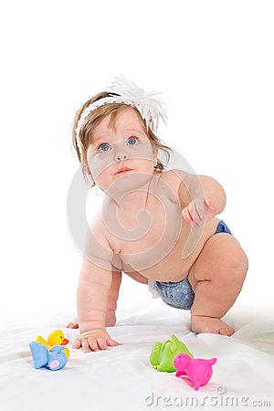 Cute baby girl plays with rubber toys