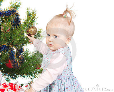Cute baby girl standing near the Christmas tree