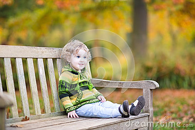 Cute baby girl on wooden bench in autumn park