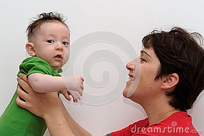 Cute baby held by his smiling mother looks toward