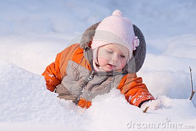 Cute baby sit in snow in forest and dig snow
