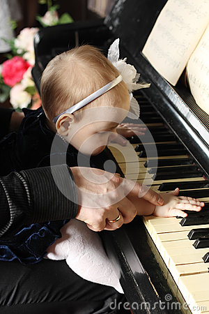 Cute baby sits at knees of father and plays piano