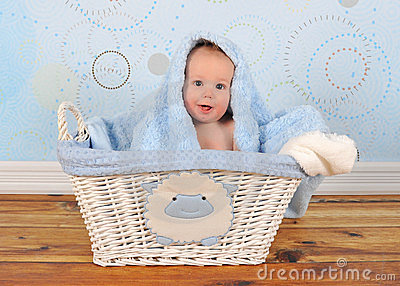 Cute baby sitting in basket with blanket on head